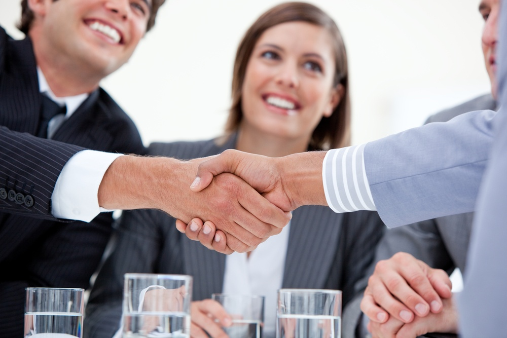 Smiling businessman and his colleague closing a deal with a partner in a meeting