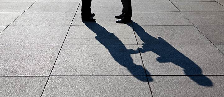 feet and shadow of people shaking hands