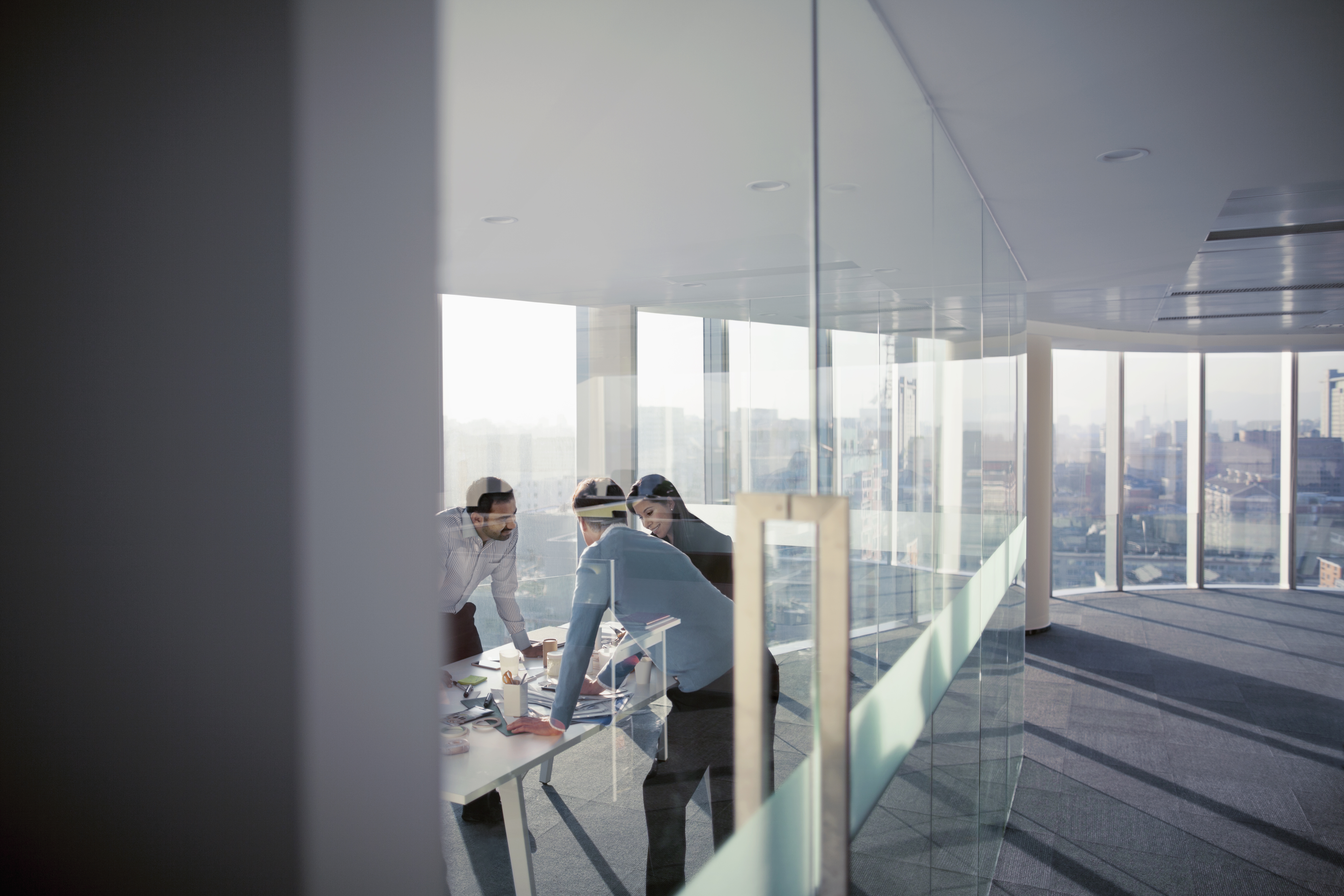 Two men and a woman crowded around a conference table in a high-rise office seen through wall of glass