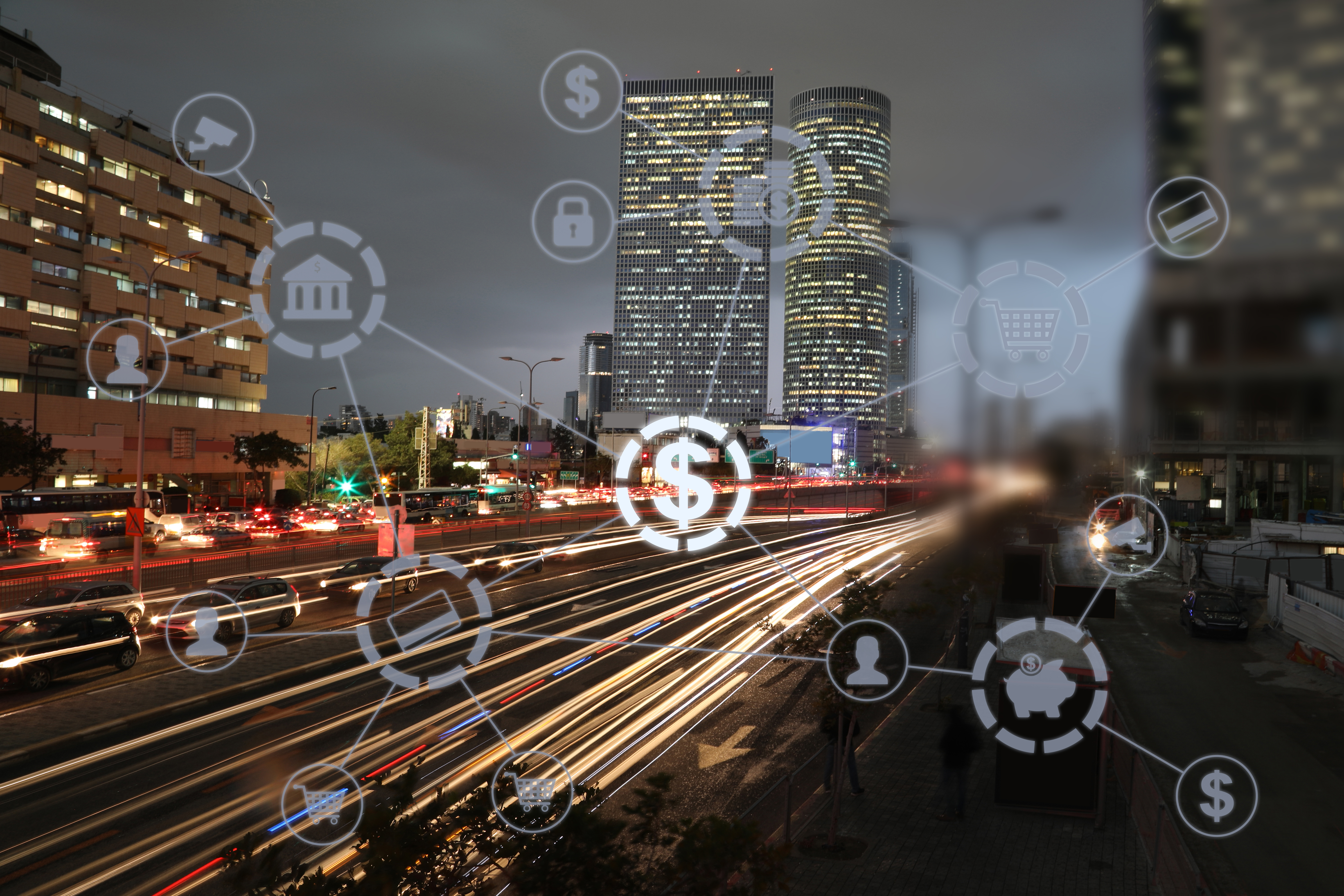 City skyscrapers and freeway at night, lit up with overlay of payment automation application icons